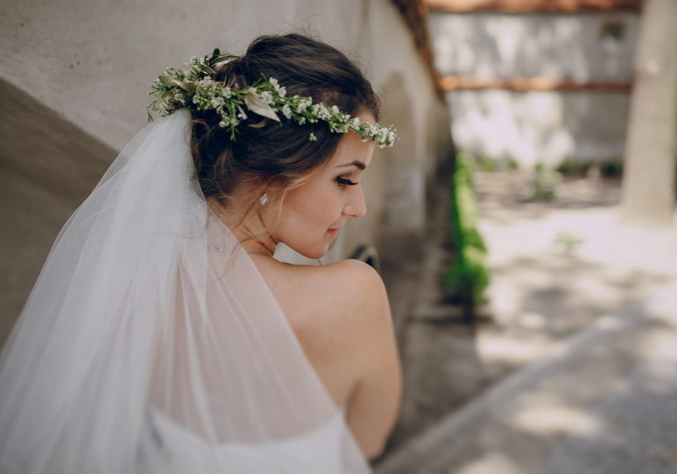 bride poses for photos in wedding dress and wreath
